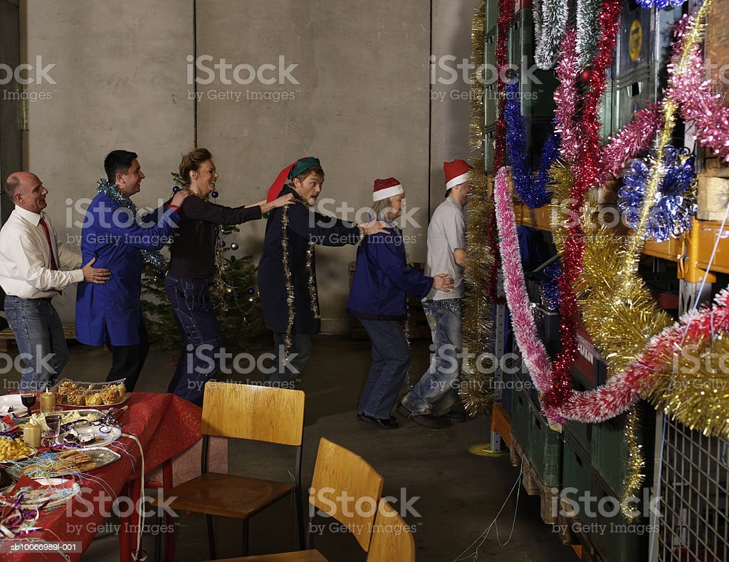 Group of warehouse workers dancing in chain formation in warehouse, side view royalty-free stock photo