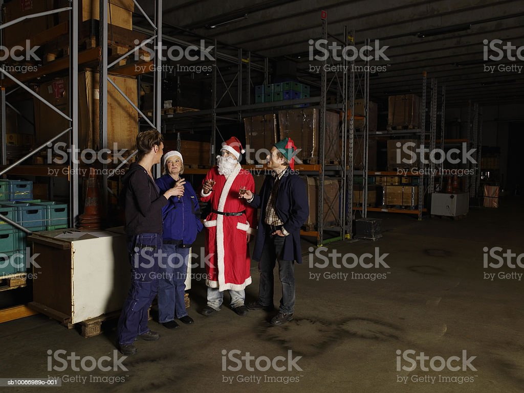Group of warehouse workers, one dressed as santa, holding wine glasses in warehouse royalty-free stock photo