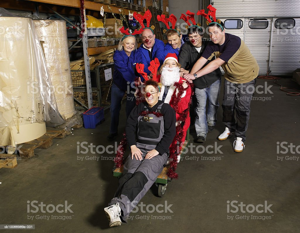 Group of warehouse workers wearing reindeer antlers pushing person dressed as santa on trolley in warehouse, portrait royalty-free stock photo
