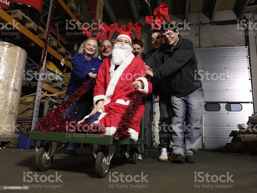 Group of warehouse workers wearing reindeer antlers pushing person dressed as santa on trolley in warehouse, portrait, low angle view royalty-free stock photo