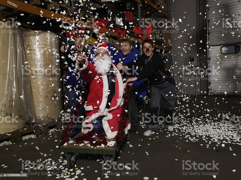 Group of warehouse workers wearing reindeer antlers pushing person dressed as santa on trolley in warehouse royalty-free stock photo