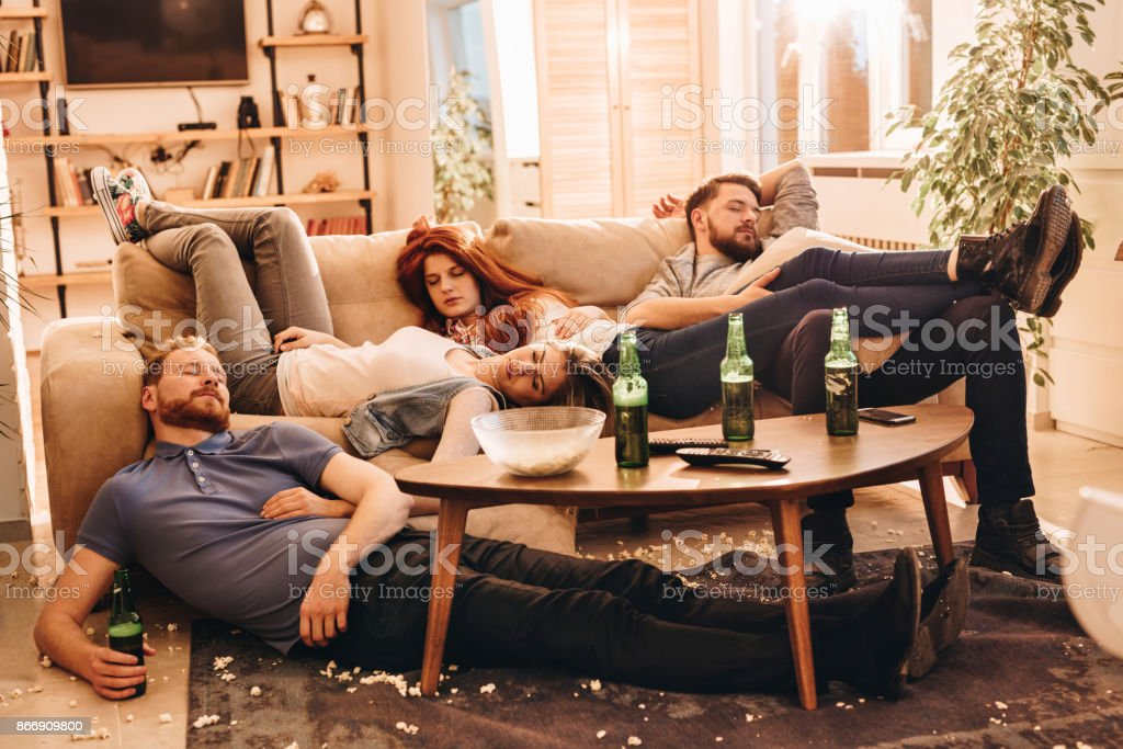 Group of wasted friends sleeping after party in the living room. stock photo