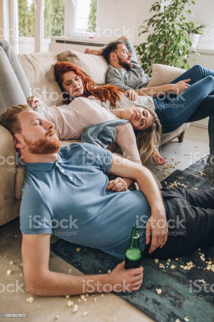 group of wasted friends sleeping after the party in the living room