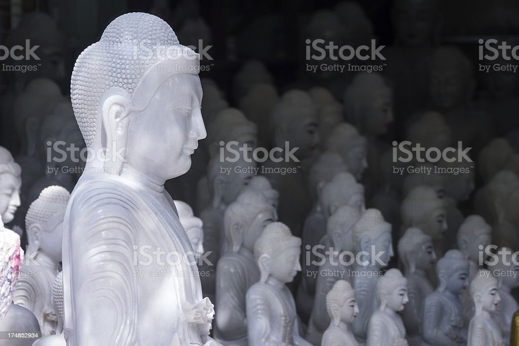 Group of white marble Buddha statues, selective focus. (Mandalay, Myanmar) stock photo
