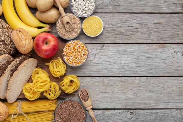 grupo de alimentos integrales y de carbohidratos en la madera - carbohidrato fotografías e imágenes de stock