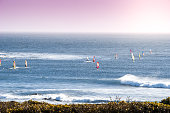 Group Of Windsurfers In The Ocean At Sunset