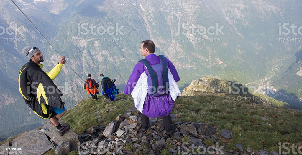 Group of wingsuit jumpers prepare to launch stock photo