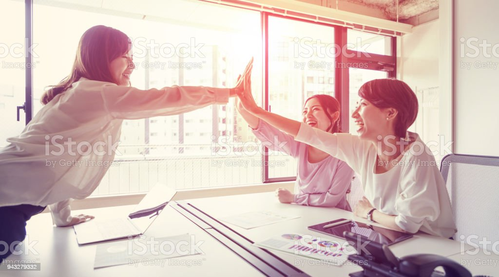 Group of woman giving high five. stock photo