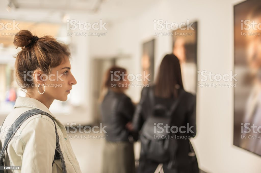 Group of woman looking at modern painting in art gallery stock photo