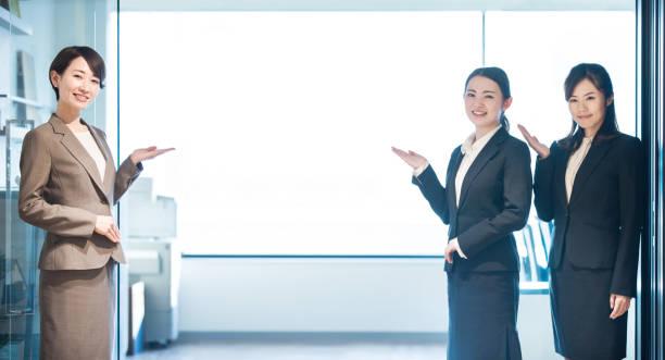 事務所の入り口に立っている女性のグループ。 - 案内 ストックフォトと画像