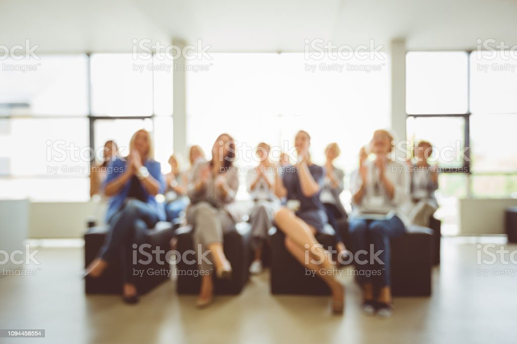 Group of women applauding during seminar Defocused group of women applauding during seminar. Blurred photo background of businesswomen group in seminar room. Admiration Stock Photo