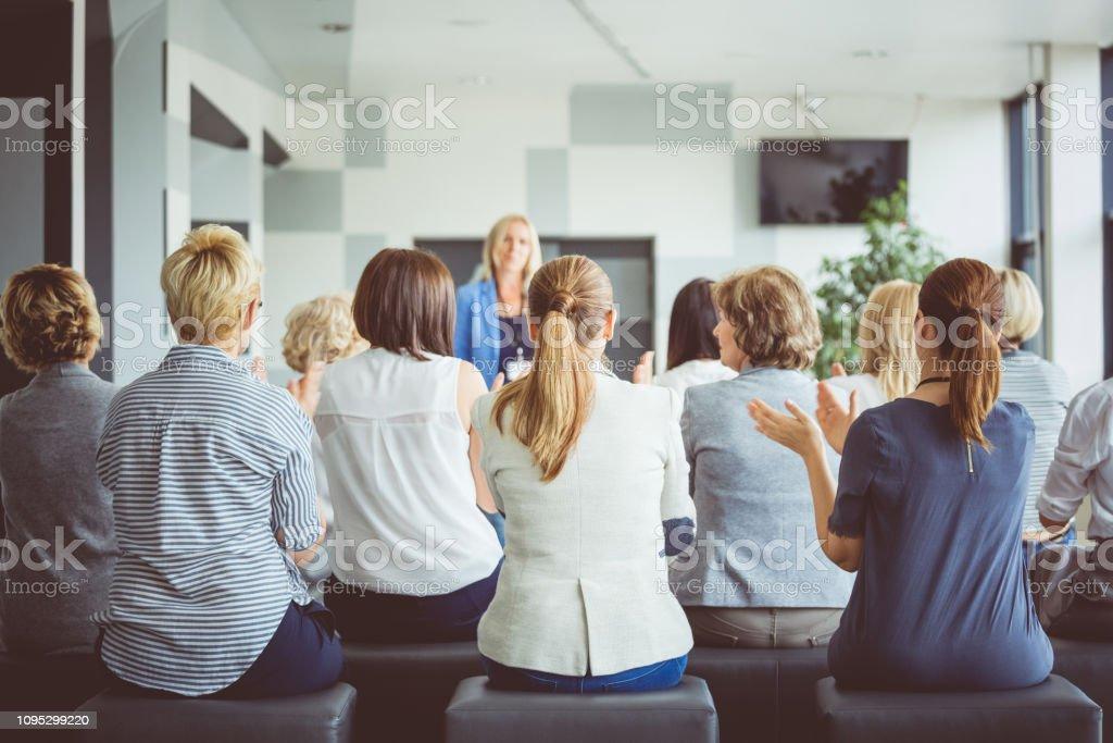 Group of women applauding the speaker in seminar Rear view of group of women applauding the speaker during seminar. Women in seminar clapping after a speech. Achievement Stock Photo