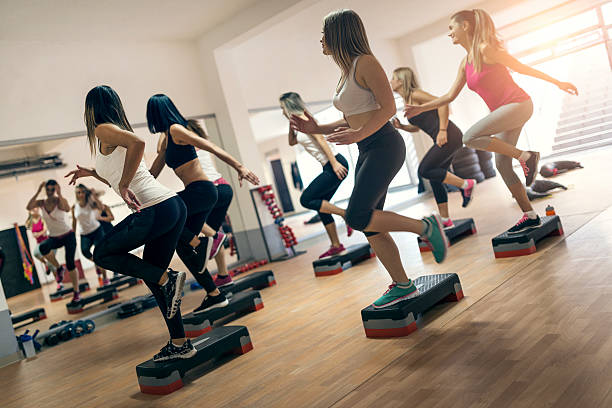 group of women at aerobics class exercising in gym - aerobics stock photos and pictures