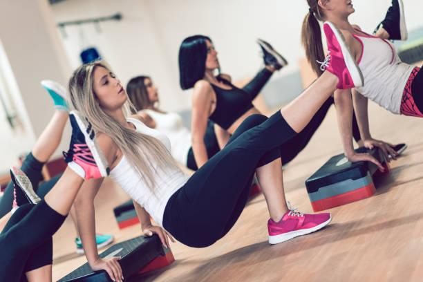 Grupo de las mujeres en clase de ejercicios aeróbicos ejercite en el gimnasio. - foto de stock
