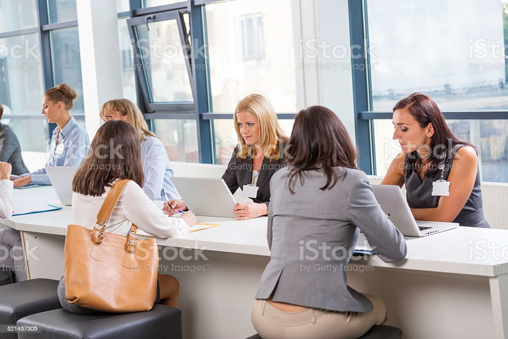 Group of women at job fair Group of women attending a job fair, sitting at the table, using laptops, working together and discussing. Adult Stock Photo