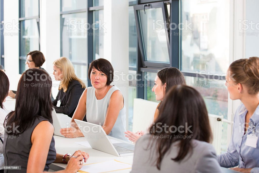 Group of women at job fair Group of women attending a job fair, working together and discussing. 2015 Stock Photo