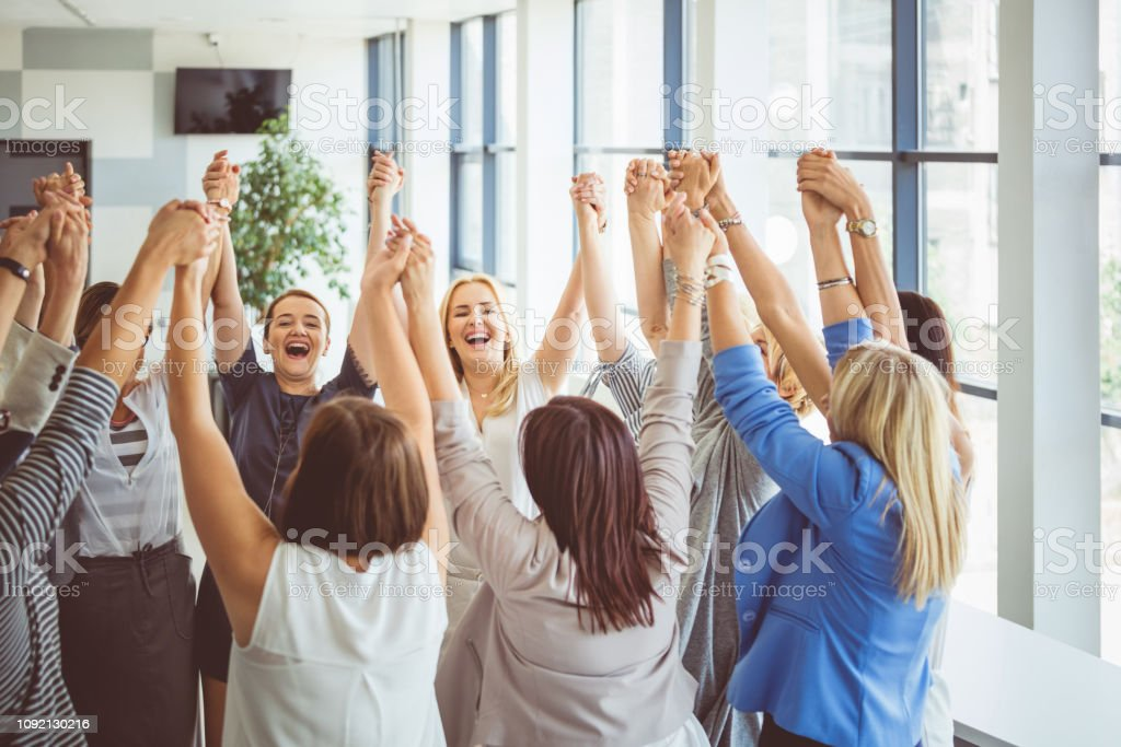 Group of women at the session on team building Happy group of females standing together and holding hands. Females showing unity and trust during a training session. Achievement Stock Photo