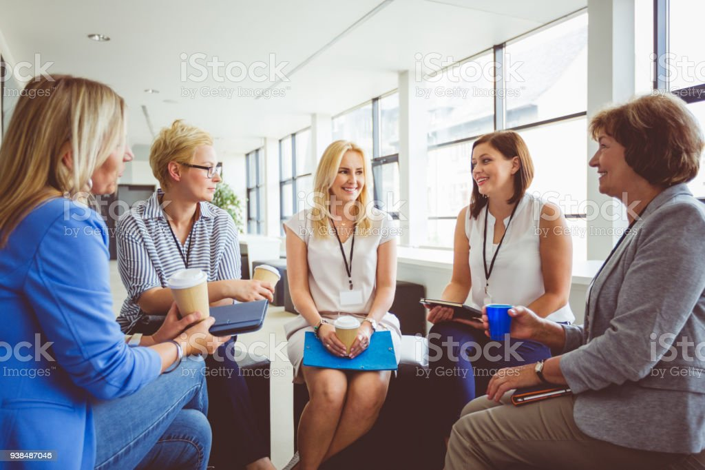 Group of women at the training, having coffee break Group of women at the training, sitting in circle and talking. Adult Stock Photo