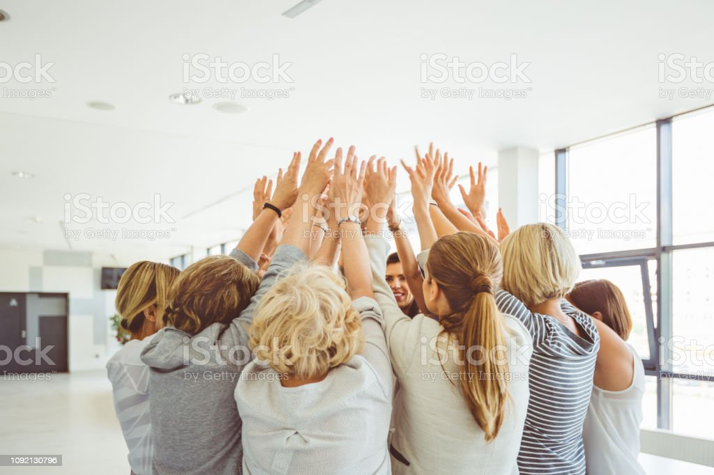 Group of women at the training Female group standing together and raising their hands in unity. Women attending a team building seminar. Achievement Stock Photo