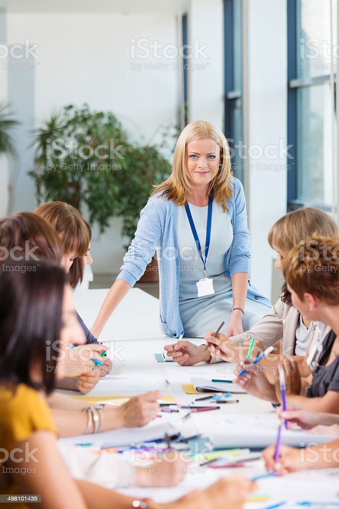 Group of women at the training Group of women attending a training, working together and discussing. Focus on the female coach smiling at the camera. 30-39 Years Stock Photo