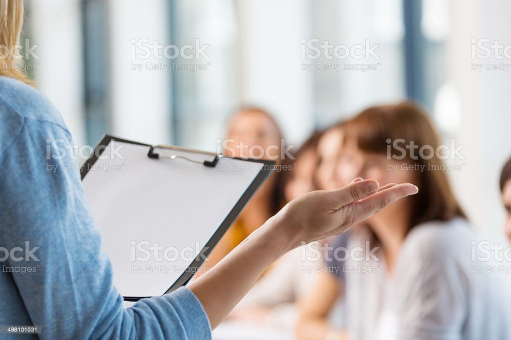 Group of women at the training Group of women attending a training. Focus on the female teacher's hand and clipboard. 30-39 Years Stock Photo
