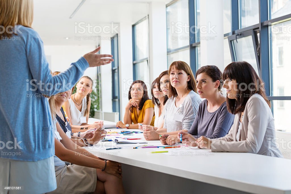 Group of women at the training Group of women attending a training, listening to the female coach. 30-39 Years Stock Photo