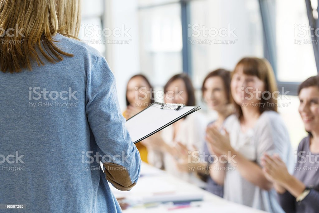 Group of women at the training Group of women attending a training and clapping hands. Back view of female teacher holding a clipboard. 30-39 Years Stock Photo