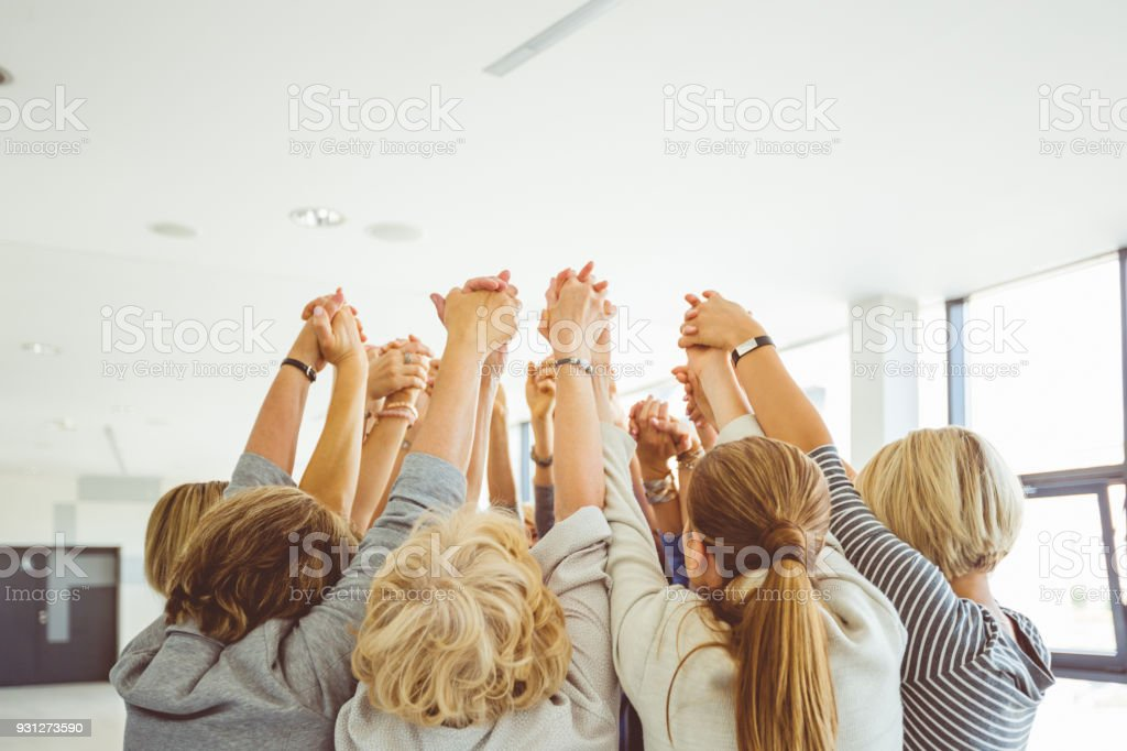 Group of women at the training Group of women at the training, raising arms together. Unrecognizable people. A Helping Hand Stock Photo