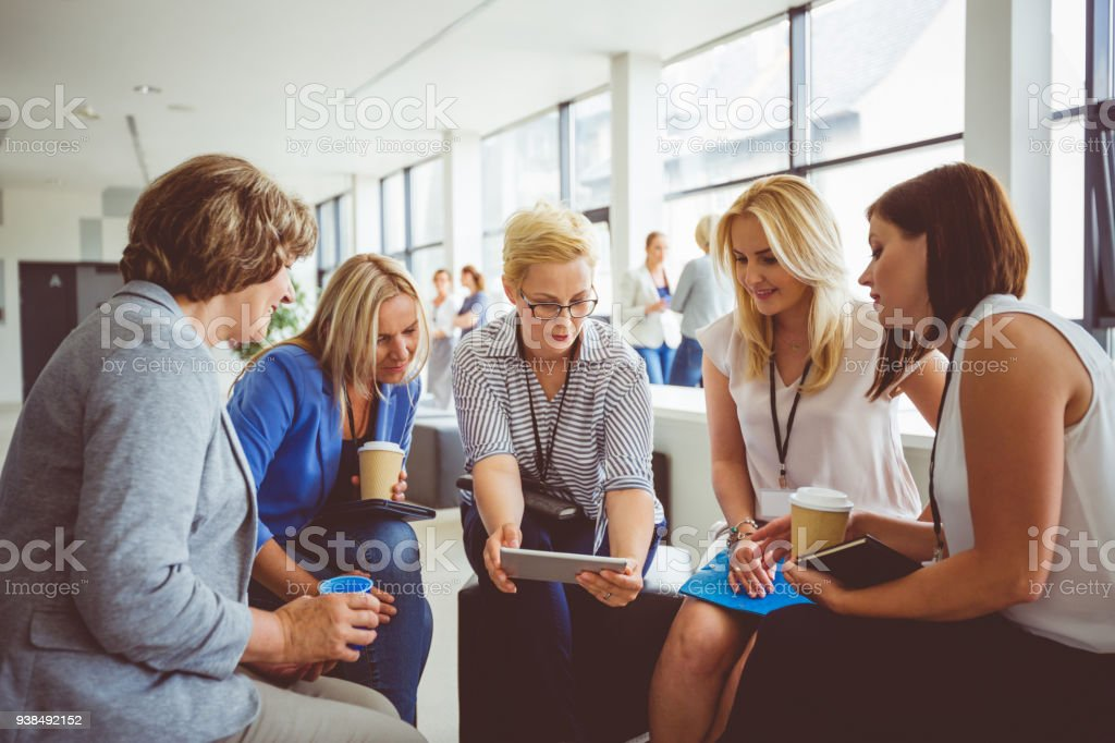 Group of women at the training Group of women at the training, sitting in circle and talking. Blonde woman holding digital tablet. Adult Stock Photo