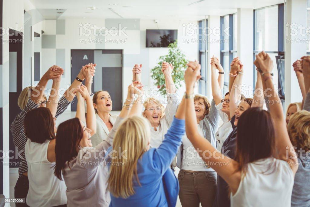 Group of women at the training, raising amrs and laughing Group of happy women at the training, raising arms together and laughing. A Helping Hand Stock Photo