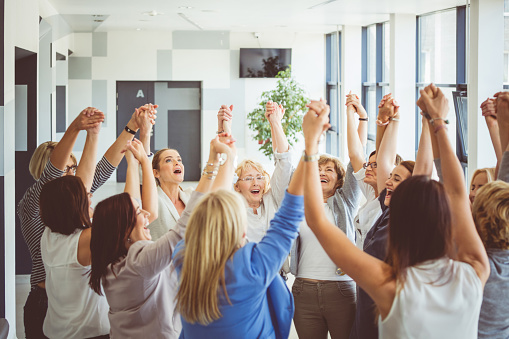 Group Of Women At The Training Raising Amrs And Laughing Stock Photo - Download Image Now