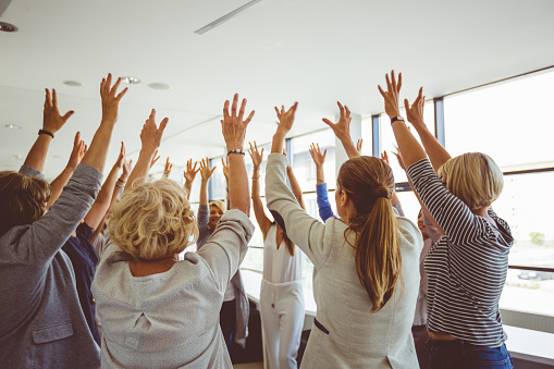 Group Of Women At The Training Raising Hands Together Stock Photo - Download Image Now