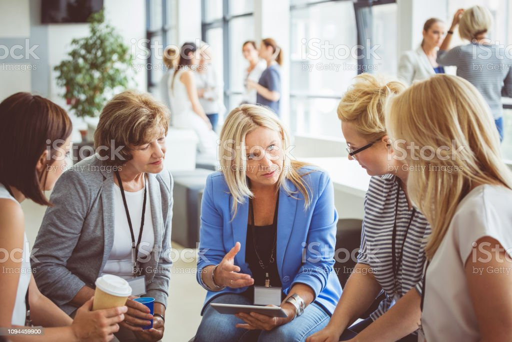 Group of women brainstorming during a training Mature woman with a digital tablet discussing new techniques with group of females in a training. Group of women brainstorming during a training session. Adult Stock Photo