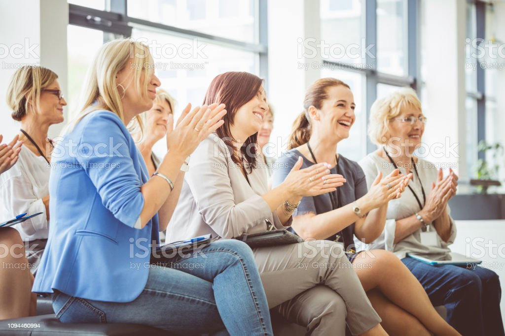 Group of women clapping at seminar Audience applauding after the successful speech by speaker. Group of women clapping at seminar. Achievement Stock Photo
