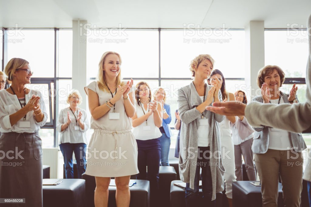 Group of women clapping hands during seminar Group of happy women clapping hands during seminar. Presenter standing in front of audience. Adult Stock Photo