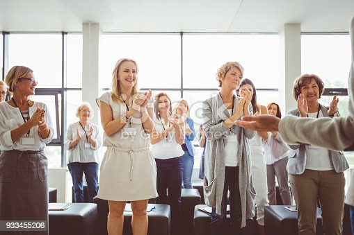 894290604 istock photo Group of women clapping hands during seminar 933455206