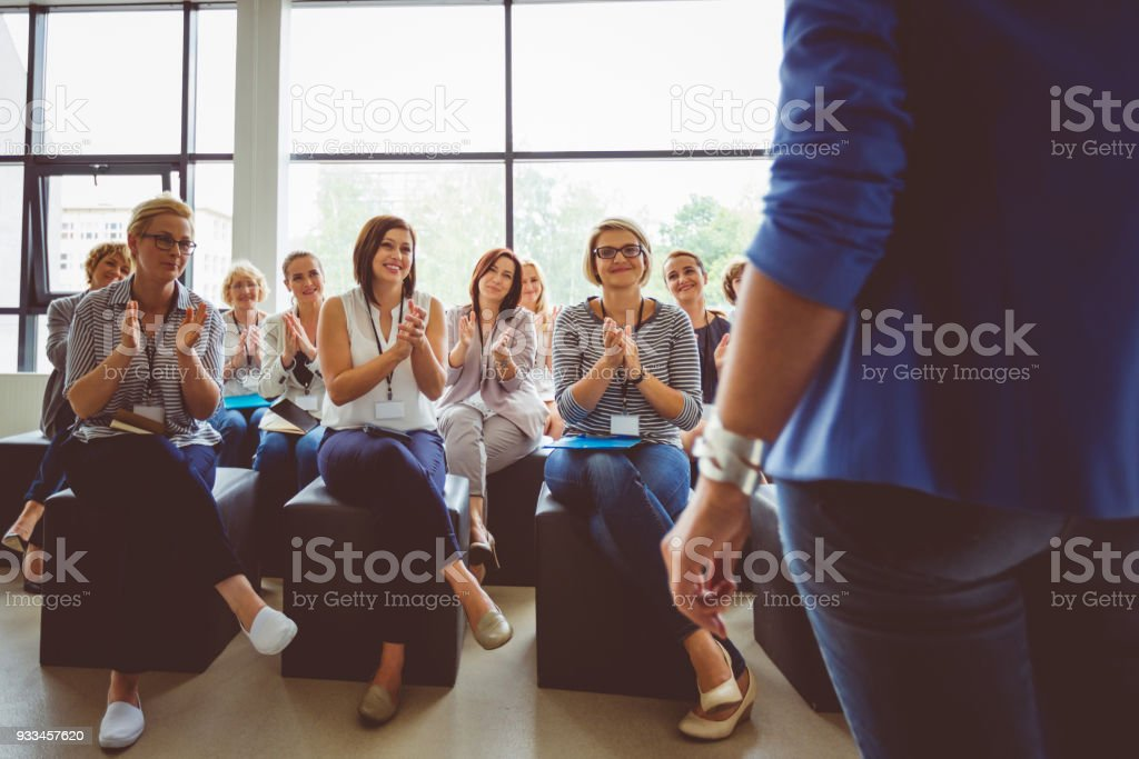 Group of women clapping hands during seminar Group of women clapping hands during seminar. Presenter standing in front of audience. Achievement Stock Photo