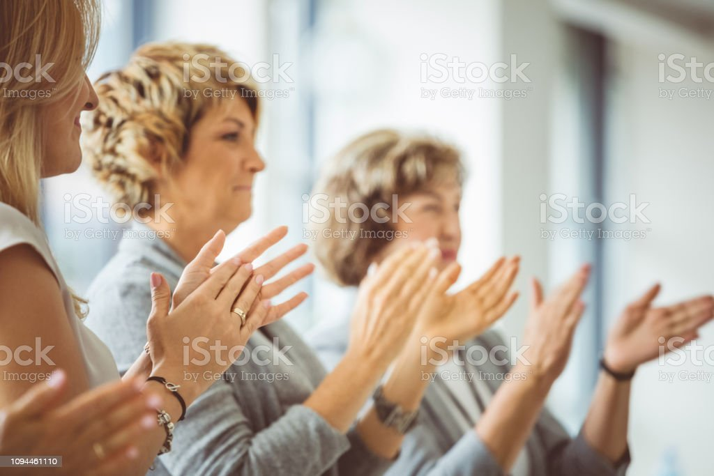 Group of women clapping hands during training session Group of women sitting and applauding after the successful speech by speaker. Group of women clapping hands during training session in conference hall. Achievement Stock Photo