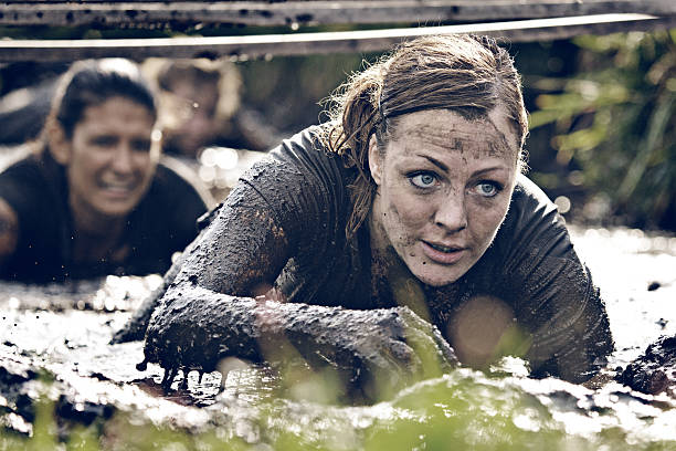 group of women crawling in mud group of women crawling in mud obstacle course stock pictures, royalty-free photos & images