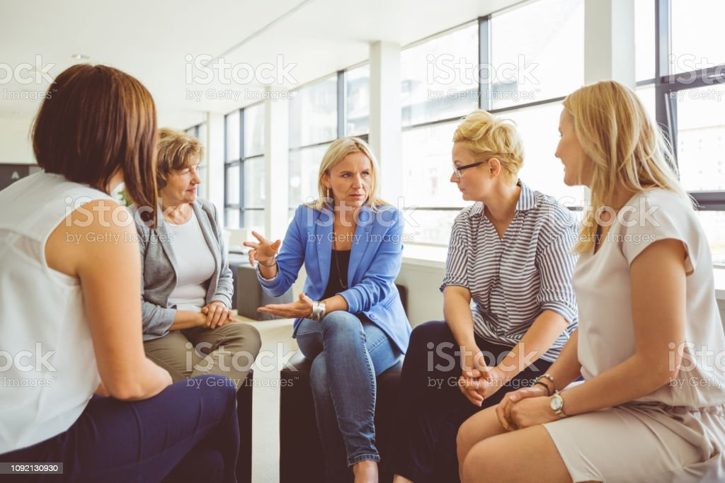 Group of women discussing at the training Group of women discussing at the training. Female group sitting together and talking. Adult Stock Photo