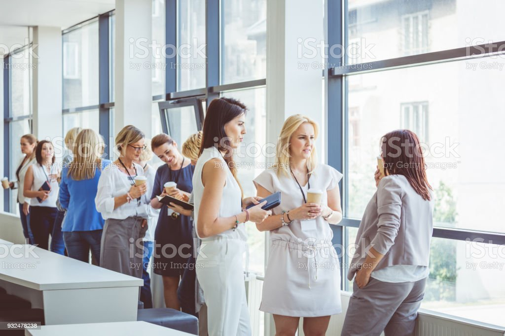 Group of women discussing during coffee break on seminar Women at conference. Group of women discussing during coffee break. Adult Stock Photo