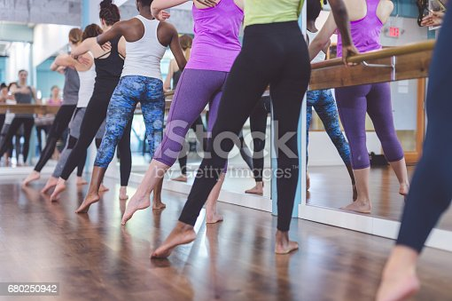 Multiethnic group of young women do barre  workout together at modern gym