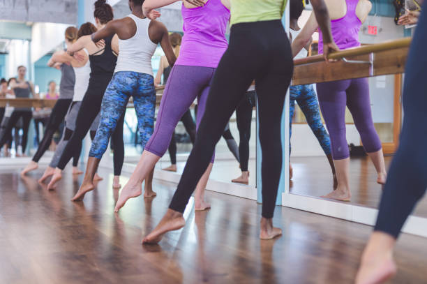 group of women doing barre  workout - dance class stock photos and pictures