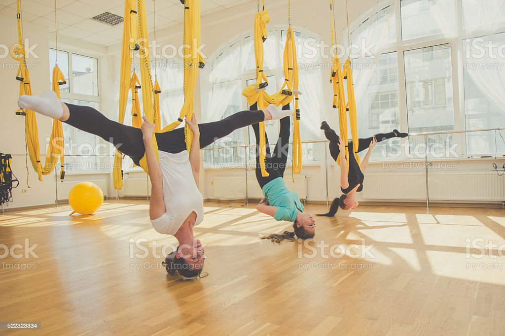 Group of women doing fly yoga sports stock photo