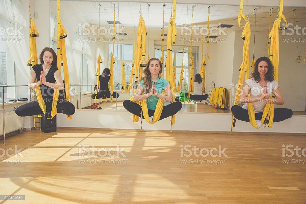 Group of women doing meditation in hammocks stock photo