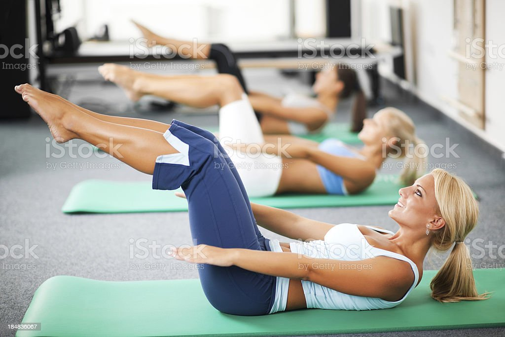 Group of women doing Pilates exercises. stock photo