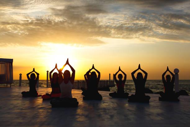 A group of women doing yoga at sunrise near the sea stock photo