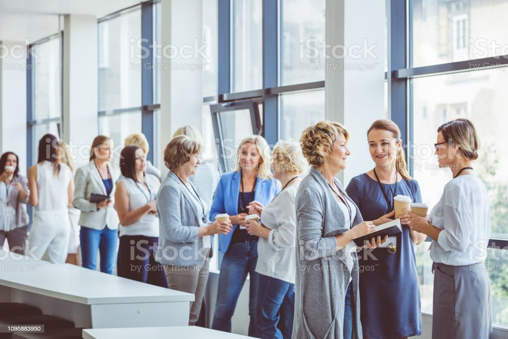 Group of women during a break in seminar Group of women during a break in seminar. Women standing in office building lobby having coffee and talking. Adult Stock Photo