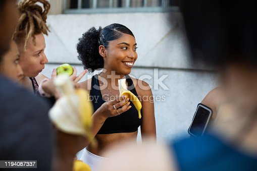 Group of women eating banana in workout training break. Happy multi-ethnic females relaxing after completing exercise session standing outdoors and eating bananas in morning.