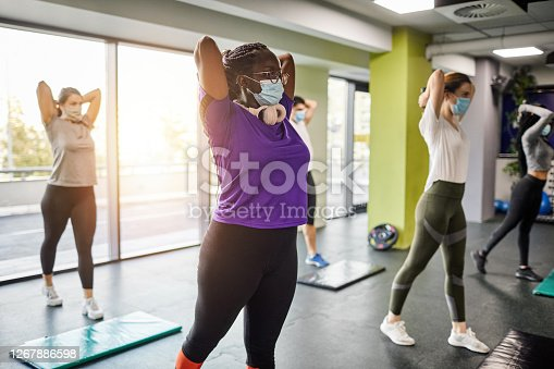 Group of women exercising with protective face masks in the gym after coronavirus pandemic. Reopening business concept.